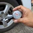 Stockfoto: Checking tire air pressure with meter gauge before traveling