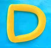 Yellow clay alphabet letter D — Stock Photo