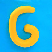 Yellow clay alphabet letter G — Foto Stock