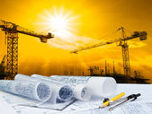 Architect plan on working table with crane and building construction background — Stock Photo