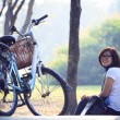 Asian woman sitting in the park with bicycle in morning use for helathy life and relaxing in holiday and vacation — Stock Photo