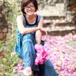 Asian woman with pink flower bouquet in her hand smilling to cam — Stock Photo #37233863