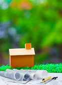 Plan compass and paper work with home on green grass with blur b — Stock Photo