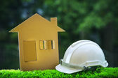 Paper home out line with safety helmet on green grass field wtih — Stock Photo