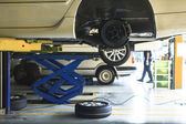 Car wheel suspension and brake system maintenance in auto serv — Stock Photo