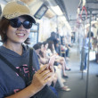 Face of woman in sky train with smart phone in hand use for city life and traveling theme — Stock Photo #37593233