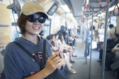 Face of woman in sky train with smart phone in hand use for city life and traveling theme — Stock Photo