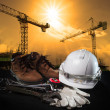Stock Photo: Helmet and construction equipment with building and crane agains