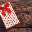 Heart spot present gift box with red ribbon on old wood texture — Stock Photo