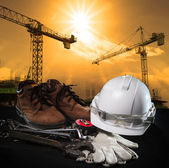 Helmet and construction equipment with building and crane agains — Stock Photo