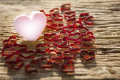 Beautiful pink heart icon with lovely red heart on old wood text — Stock Photo