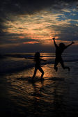 Couple jumping on the beach at dusk — Stock Photo