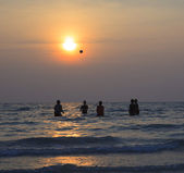 Group of people playing beach ball in sea with dusky sun set sky — Stock Photo