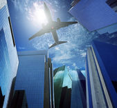 Passenger plane flying over modern office building against blue sky white cloud seem city life and air transport business scene — Stock Photo