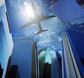 Passenger plane flying over modern office building against blue sky white cloud seem city life and air transport business scene — Stock Photo