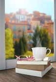 Relaxing with cup of hot drink tea or coffee and book lying besi — Stock Photo