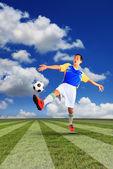 緑の芝生の上に浮かぶ男性のサッカー選手とサッカー ボール — ストック写真
