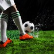 Soccer football players kicking to soccer ball on green grass field with splashing of transparent water against black background — Stock Photo #42052641
