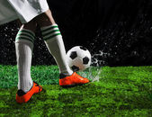 Soccer football players kicking to soccer ball on green grass field with splashing of transparent water against black background — Stock Photo