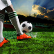 Soccer football players kicking to soccer ball on green grass field with splashing of transparent water against dusky sky and sport stadium black background — Stock Photo