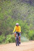 Vélo de montagne de circonscription de jeune homme en utilisation route poussiéreuse pour sport loisi — Photo