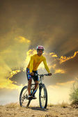 Young man riding moutain bike mtb on land dune against dusky sky in evening background  use for sport leisure and out door activities theme — Stock Photo