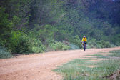 Young man riding mountain bicycle on dusty road use for helathy and cyclist activities — Stock Photo