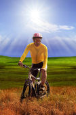 Young man wearing yellow bicycle shirt  riding mountain bike mtb — Stock Photo