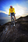 Young man riding moutain bike mtb on land dune against dusky sky — Stock Photo