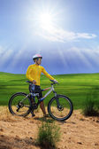 Young man standing beside moutain bike ,mtb on hill with sun shi — Stock Photo