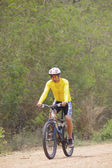 Young man riding mountain bike in dusty road use for sport leisu — Stock Photo