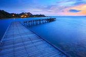 Wood bridge pier into blue sea at morning time  — Stock Photo