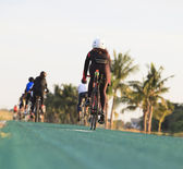 Woman riding bicycle on green track with beautiful rider suit — Stock Photo