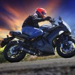 Young man riding motorcycle on curve of asphalt country road aga — Stock Photo #47308173