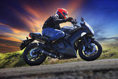 Young man riding motorcycle on curve of asphalt country road aga — Stock Photo