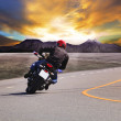 Rear view of young man riding motorcycle in asphalt road curve w — Stok fotoğraf #47650291