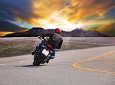 アスファルト道路曲線 w でバイクに乗って若者の背面図 — ストック写真