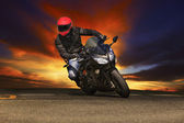 Young man riding big bike motorcycle on asphalt roads against be — Stock Photo