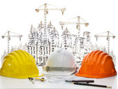 Safety helmet on engineer working table against sketching of building construction and high crane — Stock Photo