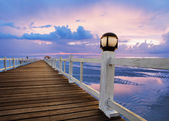 Beautiful  wood bridge pier and sea scape with dusky sky in evening — Stock Photo