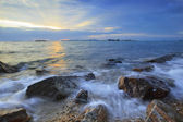 Rock sea beach with beautiful sunset over sky by long explosure photography technic — Stock Photo
