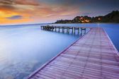 Wood bridge piers with nobody and smoothy sea water against beau — Stock Photo