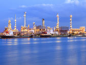 Beautiful lighting of oil refinery industry plant beside blue river use for energy industrial business theme — Stock Photo