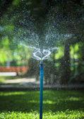 Water splashing from outdoor garden sprinkler use for freshness — Stock Photo