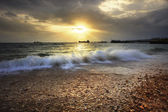 Splashing sea wave on gravel beach against sun set sky and comme — Stock Photo