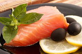 The portion of delicious salmon with basil, lemon and olives — Stock Photo