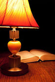 Single table-lamp and opened book — Stock Photo