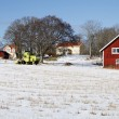 Red farmhouse, snow and winter - Stock Photo