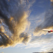 Airplane flying through dramatic clouds — Stock Photo