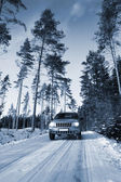 Suv, car driving through a winter landscape — Stock Photo